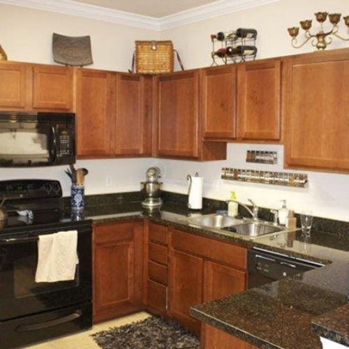 Apartment kitchen with dark wood cabinets and black countertops and black appliances